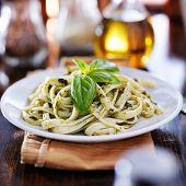 italian fettuccine in basil pesto sauce on table