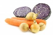 winter carrots, brown onions and a cut red cabbage on a white background