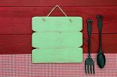 Blank antique green sign with cast iron spoon and fork