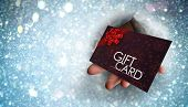 Hand bursting through paper against gift card with festive bow