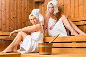 Two Women in sauna of wellness spa relaxing , enjoying an infusion