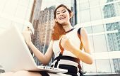 Asian business woman working outdoors with laptop om front of skyline reflection