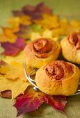 stock photo of bap  - sweet pumpkin rolls cinnamon on a background of autumn leaves - JPG