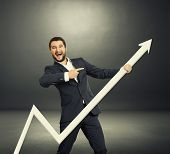 excited businessman pointing at white pointer and laughing. photo in the dark room
