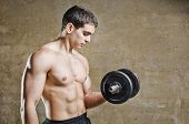 Young Fit Man Posing On Dirty Wall Background