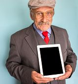 Portrait of a smiling and confident senior good looking business man holding tablet with empty display