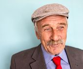 Portrait of a smiling and confident senior good looking business man with hat