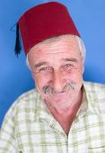 Confident elderly good looking man with fez on head