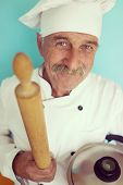 Elderly chef in white cook uniform using rolling pin