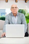 Portrait of confident senior man using laptop while sitting on couch at nursing home porch