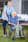 Full length portrait of male nurse standing with senior woman on wheelchair at nursing home lawn