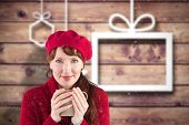 Woman holding a warm cup against blurred christmas background