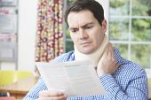 Man Reading Letter After Receiving Neck Injury