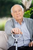 Portrait of senior man holding metal walking stick while sitting on couch at nursing home porch