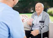image of male nurses  - Male caretaker and senior man playing cards while sitting on couch at nursing home porch - JPG