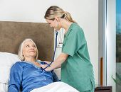 Female caretaker examining senior woman with stethoscope in bedroom at nursing home