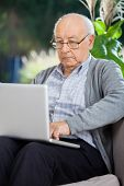 Senior man using laptop on couch at nursing home porch