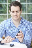 Man Checking Blood Sugar Level At Home