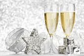 Glasses of champagne and christmas decoration on silver background