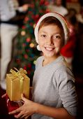 Portrait of handsome boy in Santa cap holding giftboxes