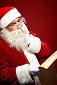 Pensive Santa Claus reading Christmas letter