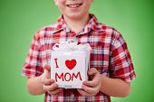 Present for mother in giftbox with note held by a boy