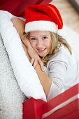 Portrait of happy girl lying on pillow and looking at camera on Christmas evening