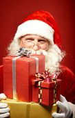 Smiling Santa Claus with pile of gifts