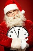 Senior man in costume of Santa holding clock showing five minutes to midnight