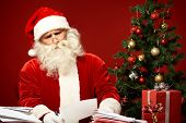 Portrait of confused Santa Claus reading letter