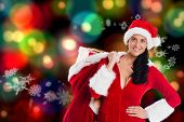 Woman smiling with christmas presents against blurred lights