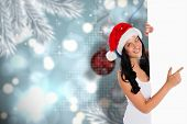 Woman pointing to large sign against baubles hanging over christmas scene