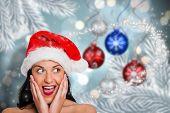 Surprised woman wearing santa hat against baubles hanging over christmas scene