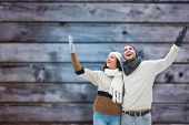 Young winter couple against blurry wooden planks