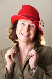 pic of lapel  - Brunette in red hat holding jacket lapels