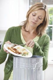 stock photo of scrape  - Woman Scraping Food Leftovers Into Garbage Bin - JPG