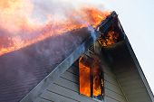 stock photo of gable-roof  - Close view of flames in an upper story window and running across the roof ridge - JPG