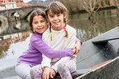 stock photo of sisters  - Two sisters are sisters are sitting in the boat and hugging