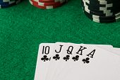 foto of flush  - clubs straight flush with poker chips on green table - JPG