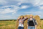 picture of sunbather  - Friends having sunbathe on large round straw bale - JPG