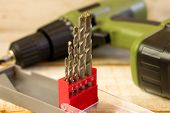 stock photo of drill bit  - Drill and set of drill bits with screws on wooden background - JPG