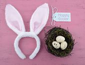 stock photo of easter eggs bunny  - Happy Easter bunny ears with Easter eggs on pink wood background - JPG