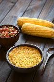 picture of corn  - Bowl of traditional Chilean corn pie called Pastel de Choclo served with Pebre sauce and corn cobs in the back photographed on dark wood with natural light - JPG