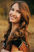 foto of auburn  - cute young woman with long auburn hair in the autumn field smiling - JPG