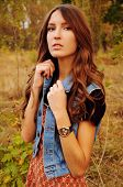 stock photo of auburn  - cute young woman with long auburn hair in the autumn forest - JPG