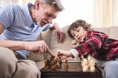 image of grandfather  - Young boy is playing chess with his grandfather at home. ** Note: Shallow depth of field - JPG