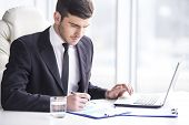 foto of handsome  - Handsome businessman is working with laptop in office - JPG