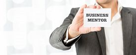 stock photo of experiments  - Businessman holding up a small white card with the words Business Mentor in a concept of consulting advice skill and experience - JPG