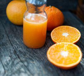 foto of orange  - Fresh orange juice and fresh oranges on a wooden table - JPG
