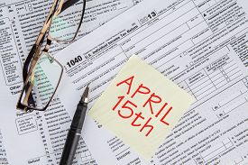 picture of time-saving  - Closeup of the deadline time of tax with the tax form and glasses - JPG